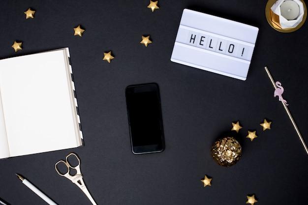 金の詳細と黒いテーブルに空の画面を持つ携帯電話