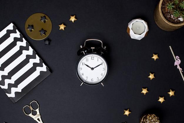 金の詳細と黒いテーブルの上の目覚まし時計