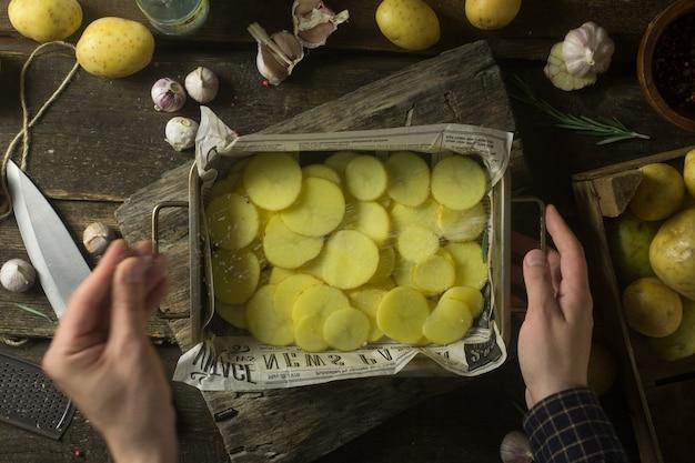 素朴な木製のテーブルで調理するための男塩スライスポテト