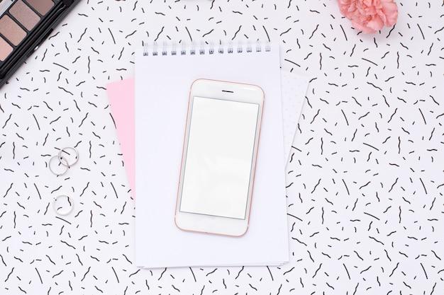 Мобильный телефон и женский блокнот с косметикой и цветком