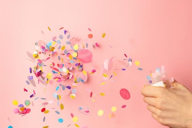 Разноцветное конфетти в женских руках на пастельном розовом фоне