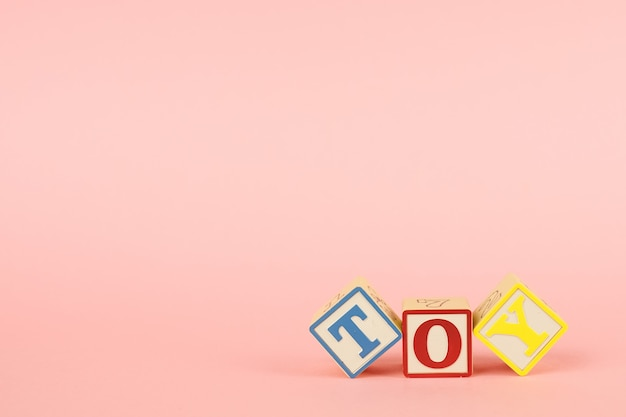 碑文のおもちゃの文字とピンクと色のキューブ
