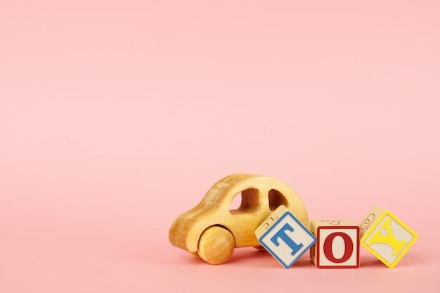 Розовый с разноцветными кубиками с буквами игрушкой и игрушечной машинкой