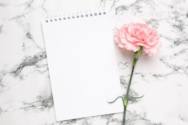 Блокнот и розовый цветок гвоздики на мраморе