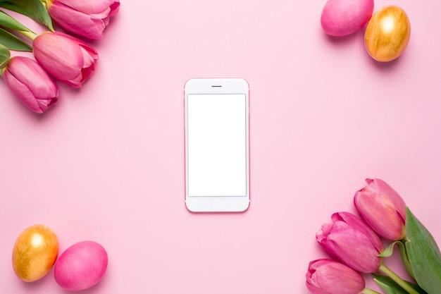 Мобильный телефон с белым экраном, пасхальные яйца и цветы тюльпанов на розовой поверхности