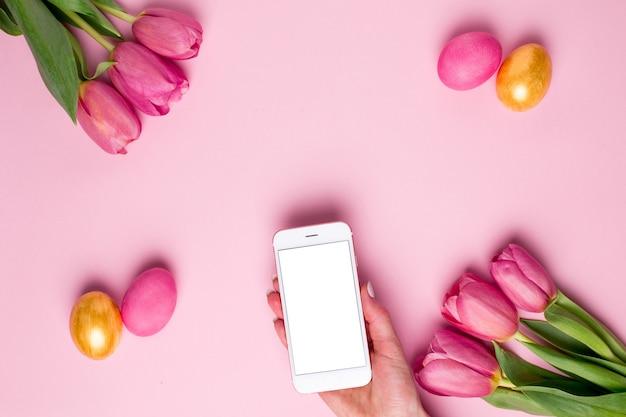 Женская рука держит телефон на розовой поверхности с цветами и пасхальными яйцами