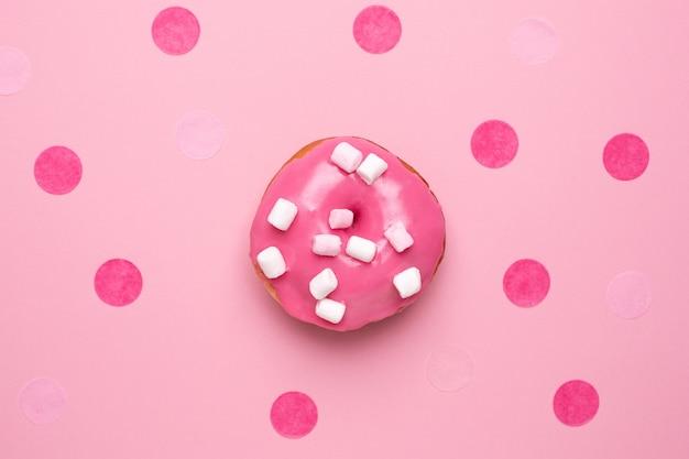 ピンクの背景のフラットにマシュマロと甘いピンクのドーナツを置く