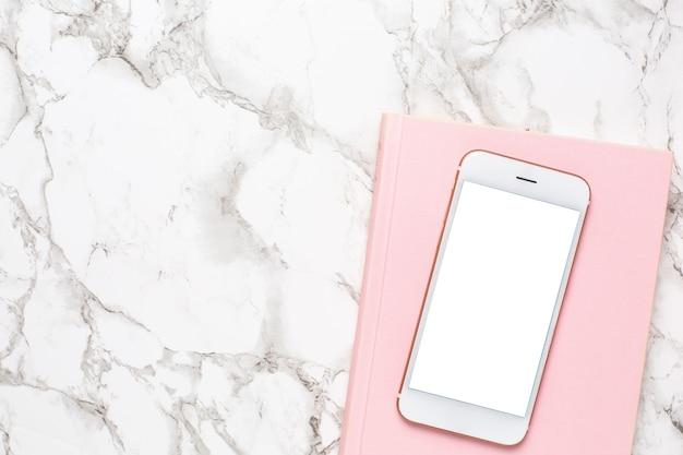 大理石の背景平面図にピンクのノートを持つ携帯電話。女性の営業日