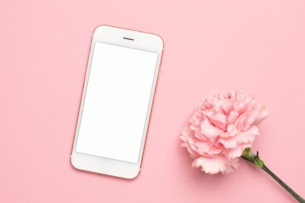 大理石の背景にピンクのカーネーションの花を持つ携帯電話
