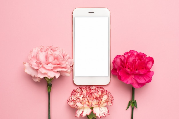 ピンクの背景にピンクのカーネーションの花を持つ携帯電話