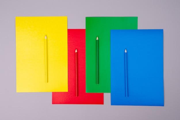 Желтые, красные, зеленые и синие карандаши с цветной бумагой на сером