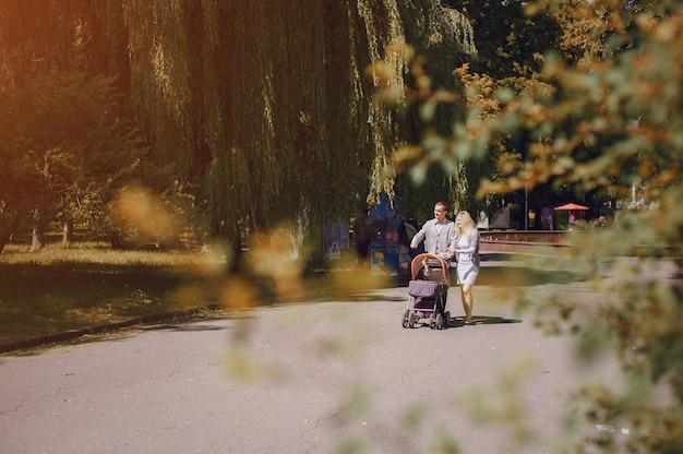 晴れた日に自分の赤ちゃんを持って歩く若い両親
