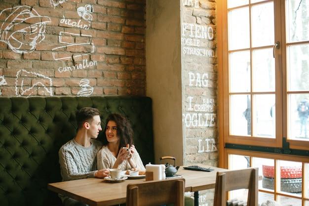 Молодая пара зимой предупреждает, сидя в кафе, пить чай и есть круассан