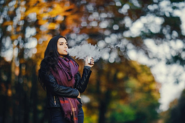 ブロンドの女の子は、タウリング秋の公園で電子タバコを吸っている