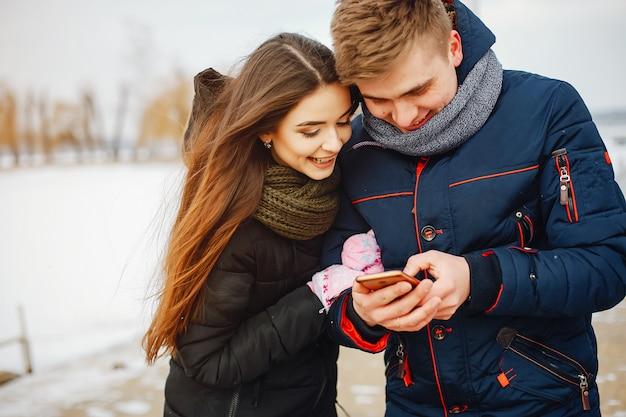 Молодая пара в зимних куртках и шарфы, стоя в снежном парке и с помощью телефона