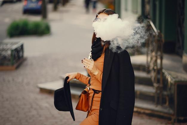 彼女が街を歩いているときに電子タバコを吸っているスタイリッシュな女の子