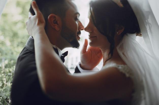 Красивый молодой человек в черном костюме, стоящий вместе со своей невестой