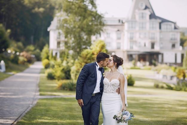 Молодая и красивая невеста и ее муж, стоящая в летнем парке с букетом