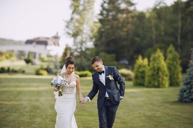 若い、美しい花嫁と花の花束と公園に立っている彼女の夫