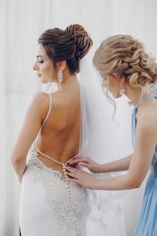 花嫁介添人と窓の近くに立つ若くて美しい花嫁