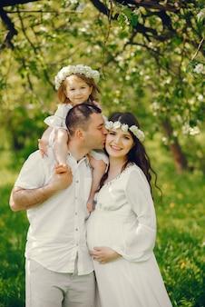 彼女のボーイフレンドと彼らの小さな娘と長い白いドレスで美しい妊娠中の女の子