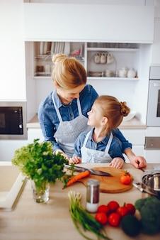 ブルーシャツとエプロンの美しい母は、自宅で新鮮な野菜サラダを準備しています