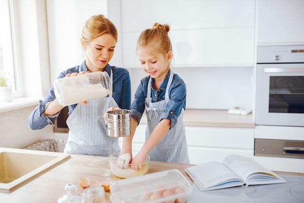 ブルーシャツとエプロンの美しい母親は台所で家で夕食を準備しています