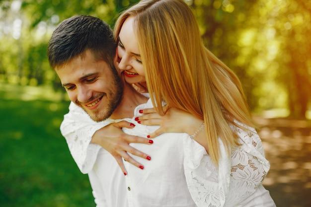 Девушка со светлыми волосами и белое платье идет в солнечном лесу со своим парнем