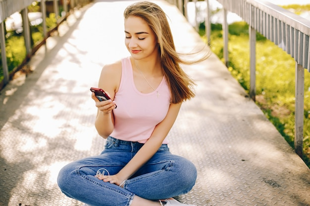 Красивая и яркая девушка в розовых майках и синих джинсах, сидящих в солнечном летнем парке