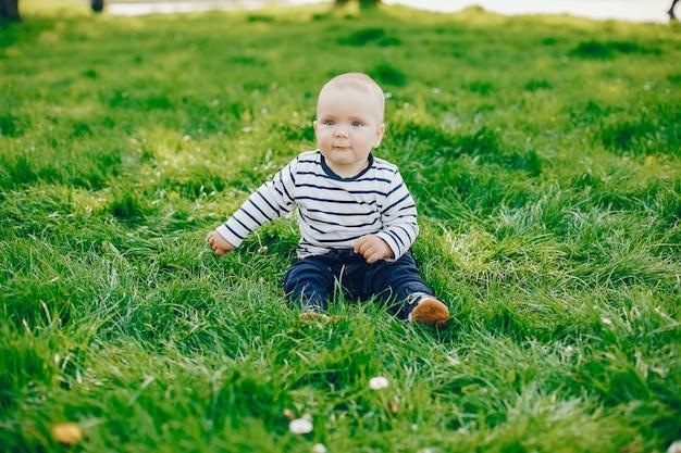 小さなかわいいハンサムな少年は、晴れた夏の公園の緑の草の上に座っている