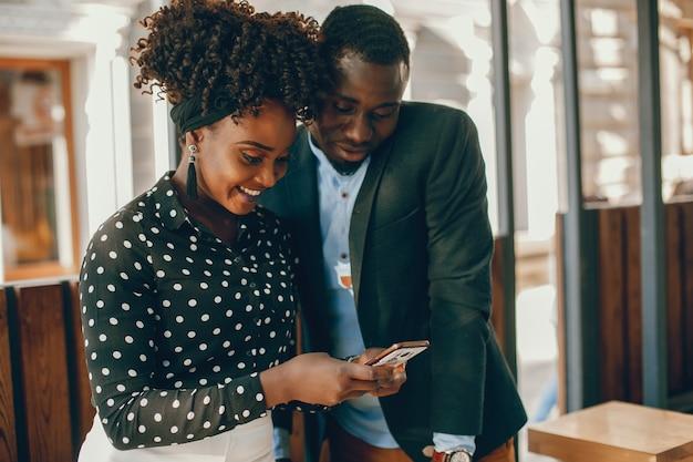 若い、スタイリッシュな暗い肌のカップルは、日当たりの良い都市に立っている