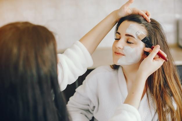 美しい手の若い女の子はブラシで彼女のガールフレンドの顔にさわやかなマスクを置きます