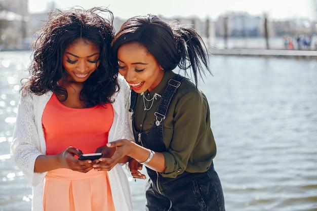 Модные черные девушки в парке