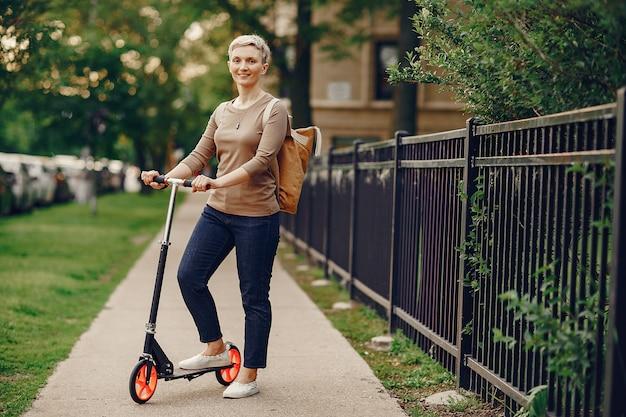 キックスクーターを持つ女性