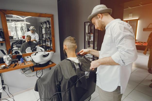 Человек режет волосы в парикмахерской.