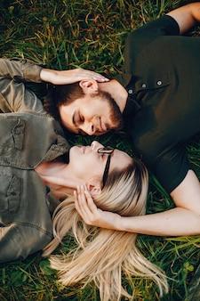 スタイリッシュな愛するカップルは、公園に横たわっています。美しい少女が彼女のボーイフレンドと楽しい時間を過ごしています