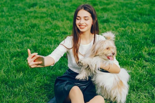 彼女は犬と一緒に公園を歩いている