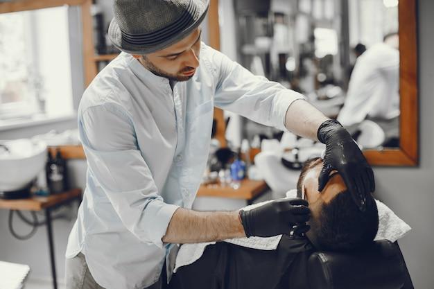 男は理髪店で彼のひげを切る。