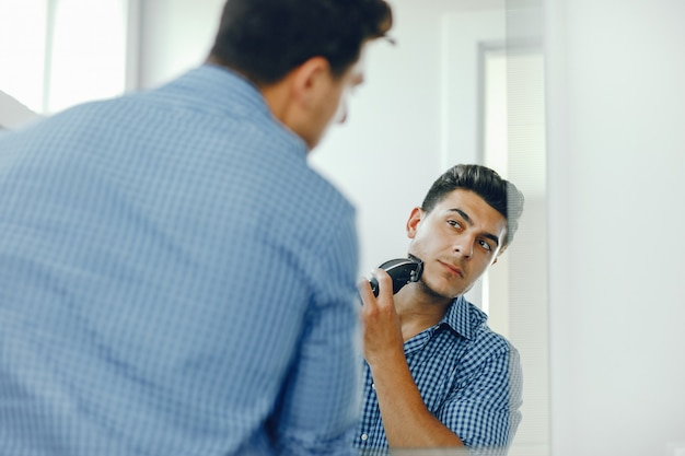男は顔を剃っている