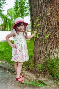 Маленькая девочка с одной стороны, опираясь на дерево