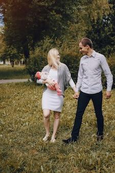 彼女は彼女の腕の中で彼女の赤ん坊を運んでいる間に男は妻と一緒に歩きます