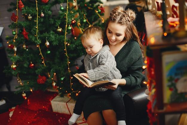 かわいい家族のクリスマスツリーのそばに座って