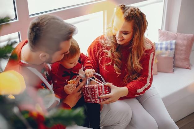家で座っているかわいい若い家族