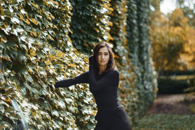 秋の間に公園を通って歩くブルネットの少女
