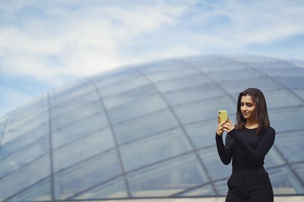 Брюнетка с мобильным телефоном во время знакомства с новым городом