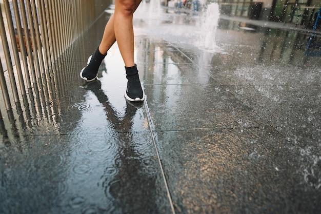 Девушка играет и танцует на мокрой улице
