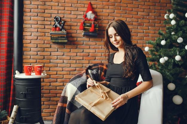 クリスマスの部屋に座っている美しい女の子