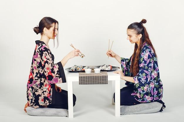 スタジオで寿司を食べている美しい女の子