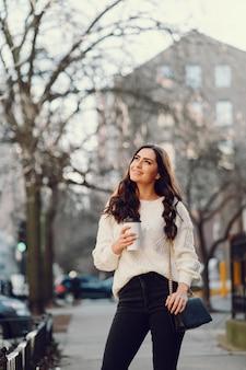 Симпатичная брюнетка в белом свитере в городе