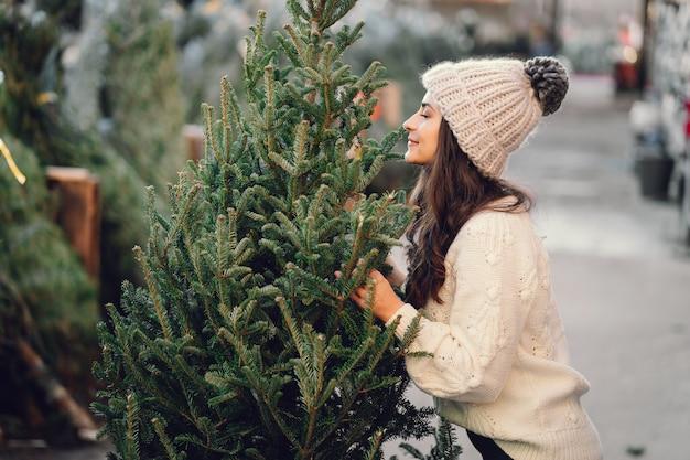 Симпатичная брюнетка в белом свитере с елкой